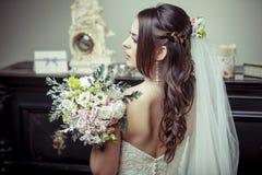 Jeune belle jeune mariée tenant le bouquet des fleurs. Image stock