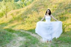 Jeune belle jeune mariée sur la canalisation verte de pelouse Photos stock