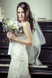 Jeune belle jeune mariée tenant le bouquet des fleurs. Photographie stock libre de droits