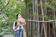 Jeune belle jeunesse adorable mignonne heureuse chinoise asiatique d'étudiant dans un jardin de parc extérieur en été photos libres de droits