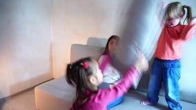 Jeune belle mère américaine s'asseyant sur le divan et travaillant dans l'ordinateur, filles luttant avec des oreillers banque de vidéos
