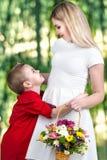 Jeune belle mère avec son fils Une femme et un bébé garçon avec un bouquet, un panier des fleurs Concept de ressort des vacances  Photographie stock