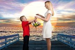 Jeune belle mère avec son fils Une femme et un bébé garçon avec un bouquet, un panier des fleurs Concept de ressort des vacances  Image libre de droits