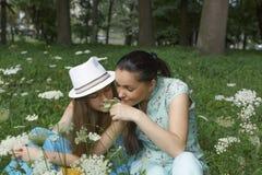 Jeune belle mère avec un sourire heureux sur son visage avec sa fille adolescente se reposant en parc sur les fleurs de renifleme Photos stock