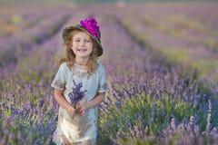 Jeune belle mère de dame avec la belle fille marchant sur le gisement de lavande un jour de week-end dans les robes et des chapea Photographie stock libre de droits