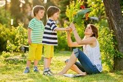 Jeune belle mère, s'asseyant dans un jardin, petits garçons, elle ainsi image libre de droits
