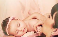 Jeune belle mère tenant avec amour son petit sleepin mignon Photographie stock libre de droits