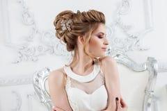 Jeune belle jeune mariée avec une coiffure élevée élégante Jeune mariée élégante dans l'intérieur luxueux, se reposant sur une ch photos stock