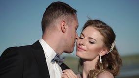 Jeune belle jeune mariée dans une robe l'épousant et toiletter étreindre et embrasser banque de vidéos