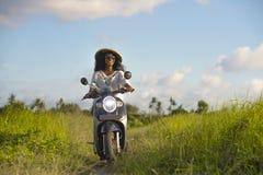 Jeune belle motocyclette afro-américaine d'équitation de femme de noir de voyageur de touriste ou de nomade dans le domaine tropi photographie stock libre de droits