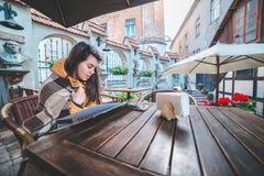 Jeune belle nourriture d'ordre de femme en café extérieur dans le matin froid photographie stock libre de droits