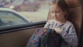 Jeune, belle passagère de fille avec le sac d'école dans l'autobus scolaire mobile utilisant le réseau social sur son smartphone  banque de vidéos