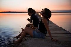 Jeune belle société des amis se reposant au bord de la mer pendant le lever de soleil Image libre de droits
