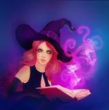 Jeune belle sorcière retenant un bok magique Photo stock