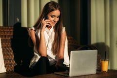 Jeune belle utilisation de fille qu'un ordinateur portable pendant elle parle au téléphone Jour ensoleillé d'été Images stock