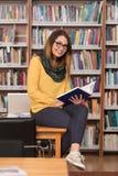 Jeune bibliothèque de Sitting At The d'étudiant photographie stock libre de droits