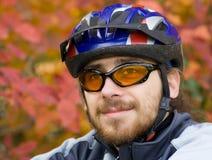 Jeune bicycler sur le fond des lames d'automne Photographie stock