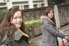 Jeune bicyclette asiatique d'équitation de femme avec des amis Images libres de droits