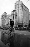 Jeune bicyclette de tour de garçon avec le fond de gratte-ciel Photographie stock