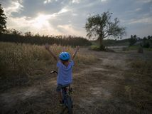 Jeune bicyclette de tour de garçon heureuse le soir avec le coucher du soleil photo stock