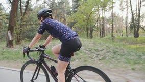 Jeune bicyclette femelle d'équitation de cycliste en parc comme partie de sa routine s'exerçante Le côté suivent le tir Mouvement banque de vidéos