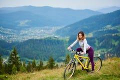 Jeune bicyclette heureuse d'équitation de femme dans les montagnes au jour d'été photos libres de droits
