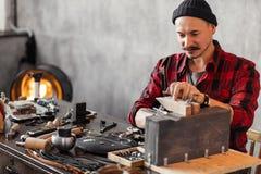 Jeune bijoutier sciant la chaise pour un client photo libre de droits