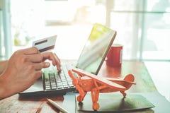 Jeune billet de fligth de salaire d'homme d'affaires en ligne sur son ordinateur portable et employer la carte de crédit se repos Images stock