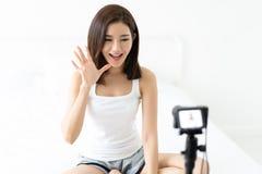 Jeune blogger asiatique de femme disant salut et ondulant avec l'enregistrement vi photos libres de droits