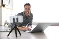 Jeune blogger avec la vidéo d'enregistrement d'ordinateur portable sur le plancher images libres de droits