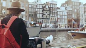 jeune blogger de la beauté 4K travaillant avec l'ordinateur portable amsterdam Liberté Fille avec le sac à dos rouge dans le chap clips vidéos