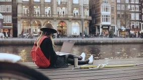 jeune blogger de la mode 4K s'asseyant avec l'ordinateur portable Travailleur créatif dehors Liberté Mode de vie tiré par une rou clips vidéos