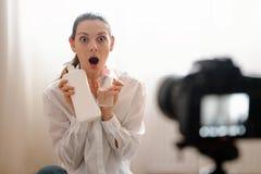 Jeune blogger féminin avec le produit vlogging de soin de corps de rewievs de dslr de caméra dans le travail en ligne moderne de  images libres de droits
