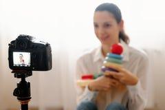 Jeune blogger féminin avec le travail en ligne moderne vlogging de jouets d'enfants de bébé de rewievs de dslr de caméra photo stock