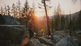 Jeune blogger masculin réussi sautant outre d'une grande pierre de forêt, hausses sur des roches à stupéfier le mouvement lent de clips vidéos