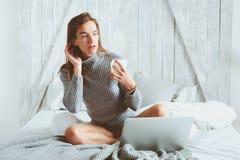 Jeune blogger ou femme d'affaires travaillant à la maison avec le media social, café potable dans le début de la matinée dans le  image libre de droits