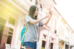 Jeune blogger ou randonneur de déplacement asiatique employant l'application d'itinéraire au téléphone portable pour trouver l'ad Images libres de droits