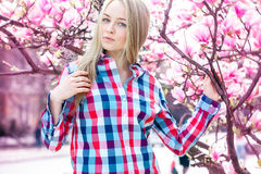 Jeune blonde attirante avec des yeux bleus regardant l'appareil-photo près du bl Image libre de droits