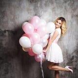 Jeune blonde avec du charme dans une robe blanche avec la ceinture rose, tenant un grand paquet de ballons Sur le fond texturisé  photo stock