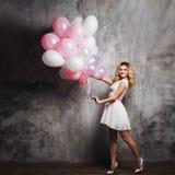 Jeune blonde avec du charme dans une robe blanche avec la ceinture rose, tenant un grand paquet de ballons Sur le fond texturisé  photographie stock libre de droits