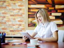 Jeune blonde dans le bureau fonctionnant derrière le comprimé Photographie stock libre de droits