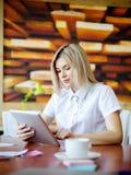 Jeune blonde dans le bureau fonctionnant derrière le comprimé Images libres de droits
