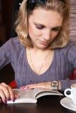 Jeune blonde dans un café affichant un livre Images libres de droits