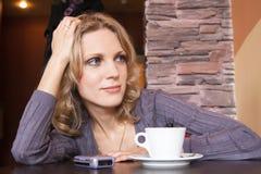 Jeune blonde dans un café attendant un appel Photos stock