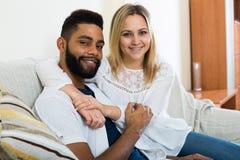 Jeune blonde et ami caressant sur le divan à la maison Photos stock