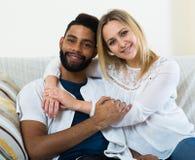 Jeune blonde et ami caressant sur le divan à la maison Images libres de droits