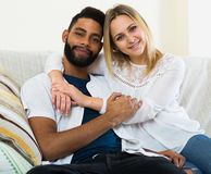 Jeune blonde et ami caressant sur le divan à la maison Photographie stock libre de droits