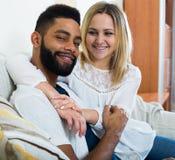 Jeune blonde et ami caressant sur le divan à la maison Photo libre de droits