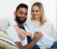 Jeune blonde et ami caressant sur le divan à la maison Image libre de droits