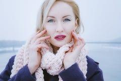Jeune blonde féminine qui utilise une grande écharpe gonflante Photographie stock